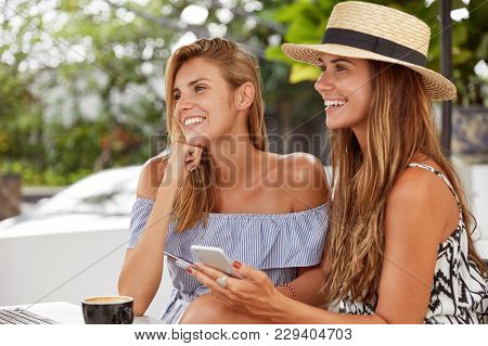 Cute Lovely Young Females With Positive Smiles Spend Free Time At Cafeteria, Use Modern Technologies