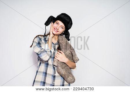 Happy Beautiful Russian Girl In Fur Hat Holds Warm Winter Felt Boots
