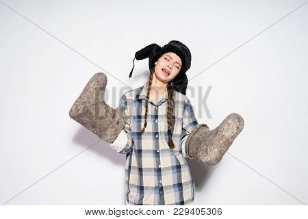 Funny Russian Girl In A Warm Fur Hat Holds Winter Gray Felt Boots