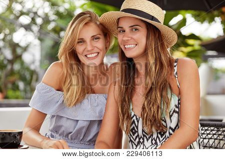 Happy Female Best Friends Sit At Outdoor Restaurant, Have Broad Smiles, Don`t See Each Other For Lon