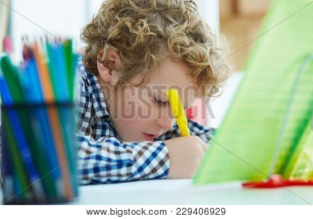 Close-up Portrait Of Curly Caucasian Little Boy Writting In Notebook. Child Sitting At The Desk At H