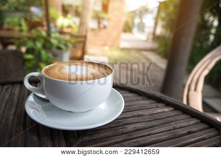 A White Cup Of Hot Latte Coffee With A Heart Latte Art On Vintage Wooden Table With Blur Green Natur