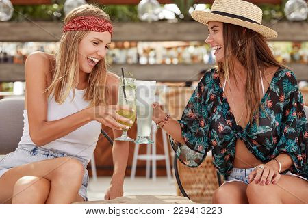 Beautiful Overjoyed Young Females Have Summer Party Together, Clink Glass Of Cocktails, Enjoy Good R