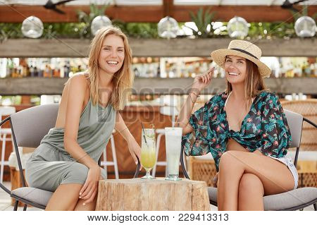 Positive Young Females Sit At Outdoor Cafeteria Or Bar, Drinks Fresh Summer Cocktails, Have Pleasant