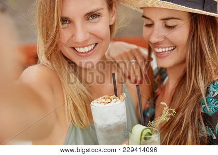 Close Up Shot Of Beautiful Young Females Have Broad Smiles, Demonstrate White Teeth, Drink Cocktails