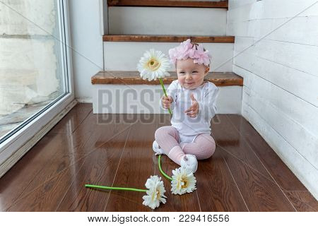 Little Smiling Baby Girl One Year Old With Wreath Siting On The Floor In Bright Room Near Window And