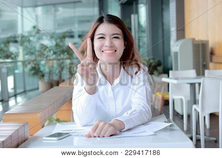 Cheerful Young Asian Business Woman Holding Two Finger As Sign As Fighting With Job At Office.