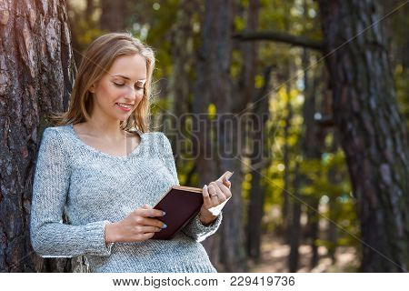 Beautiful Blond Girl Resting In Spring Or Autumn Forest Read Book And Standing. Confident Caucasian