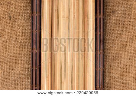 Dark And Light Bamboo Mat In The Form Of A Scroll Lie On The Sacking. View From Above.