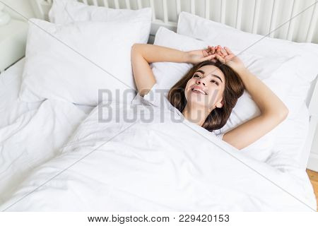 Picture Of Young Happy Woman Dressed Lies On Bed At Home Indoors.