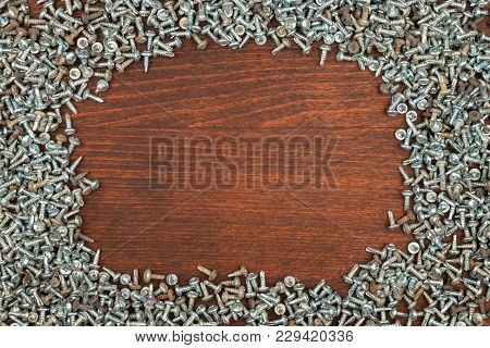 Frame Of Silver Screws Lying On A Dark Wood. View From Above