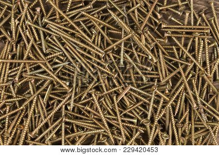 Background Of Golden Screws. View From Above. Industrial Background
