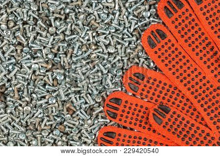 Orange Work Gloves Lying On The Background Of Screws. View From Above