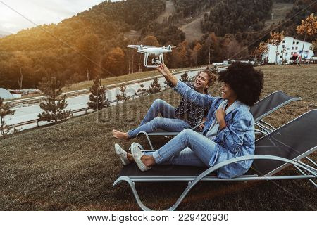 Two Beautiful Laughing Girls (the Black One And Caucasian One) Are Holding Flying Drone Which Is Sho