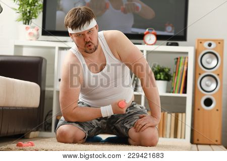 A Young Handsome Man With Excess Weight Makes The First Fitness Training At Home On Carpet Raises Th