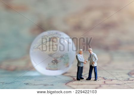 Miniature People: Businessman Handshake On The World Map With Globe. Commitment, Agreement, Investme