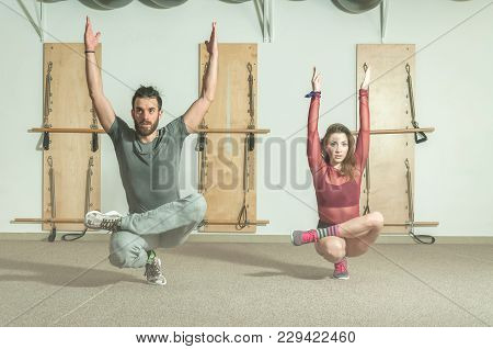 Young Beautiful And Attractive Fitness Couple Workout On Their Balance By Standing On The One Leg In