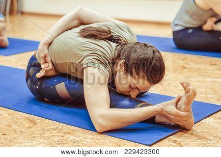 Beautiful Girl In Sportswear Is Doing Yoga On Yoga Mat In Sports Hall