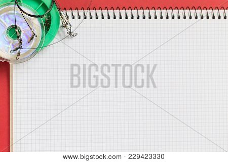 Big Notebook With Fishing Tackles On Color Paper Background