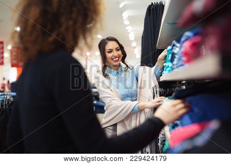 Two Young Girls Look At Clothing In Store