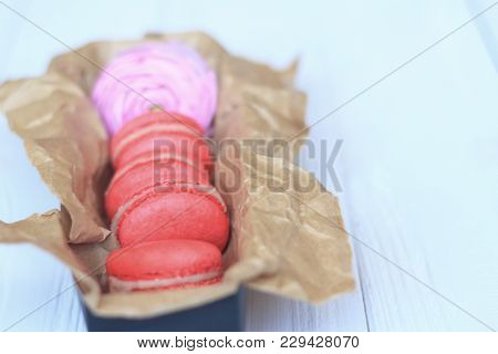 Colorful Macaroons And Flowers On Table. Sweet Macarons In Gift Box. Top View
