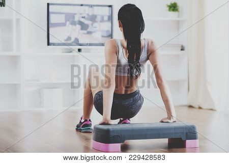 Rear View Of A Young Woman Doing Home Exercises While Watching Program On Television