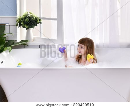 Happy Little Baby Girl Sitting In Bath Tub Playing With Duck Toys In The Bathroom. Portrait Of Baby