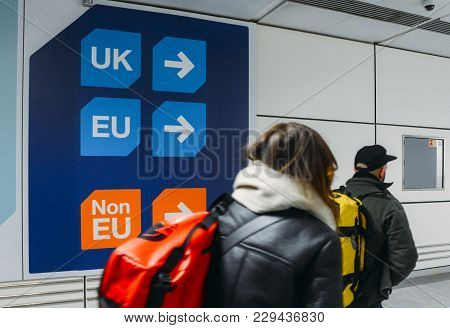 London Gatwick, March 2nd, 2018: Passengers Walks Past Sign Prior To Immigration Control Pass A Sign