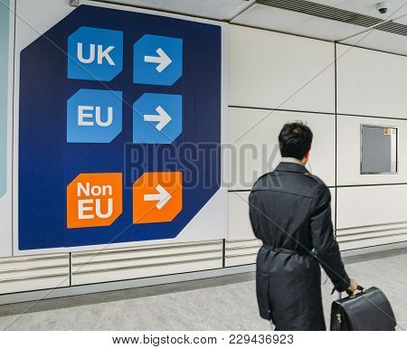 London Gatwick, March 2nd, 2018: Passenger Walks Past Sign Prior To Immigration Control Pass A Sign