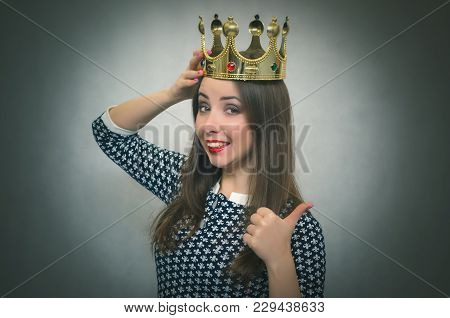 Happy Woman Is Holding In Hands A Golden Crown Above Her Head And Shows A Thumb Up. Winner Concept.