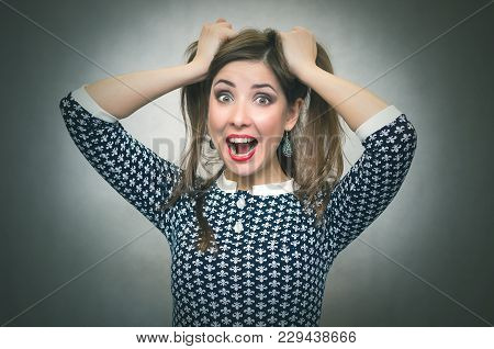 Surprised Woman In Shock Is Holding Her Hair On A Head By Her Hands And Is Screaming Isolated On Gra