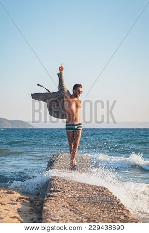 Happy Young Man Dancing On The Dock At The Beach
