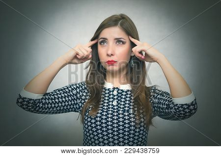 Pensive Woman Is Thinking And Try To Solve A Problem Isolated On Gray Background. Meditative Wistful