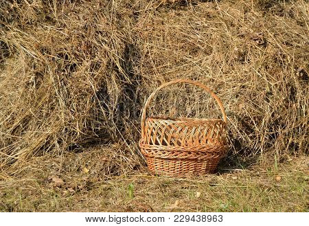 Wicker Basket Near Hay Stack On A Hot Sunny Summer Day.