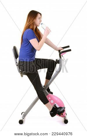 Young Woman Drinking Water On An Exercise Bike