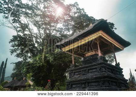 Bali Temple Amid Green Lush Tree And Tropical Forest At A Cloudy Noon Day