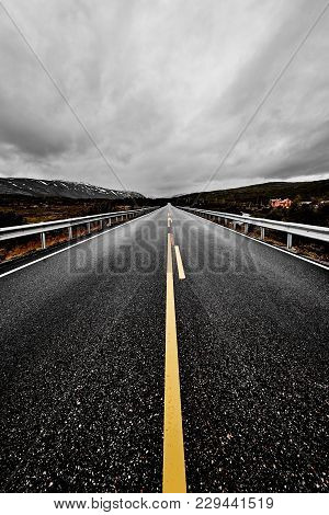 Image Of A Wide Open Prairie And Mountains With A Paved Highway Road Stretching Out As Far As The Ey