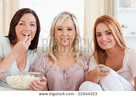 Smiling Friends Lounging On A Sofa Watching A Movie