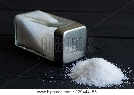 Glass Salt Shaker On Black Rustic Table And Heap Of Salt Crystals With Space For Text In Background