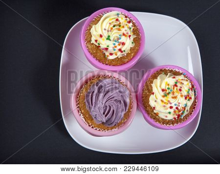 The Cupcakes With White And Violet Cream On The Black Background,
