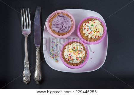 The Cupcakes With White And Violet Cream With Spoons On The Black Background, Arranged For A Party O