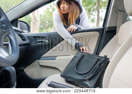 Woman Burglar Steal A Shoulder Bag Through The Window Of Car - Theft Concept.