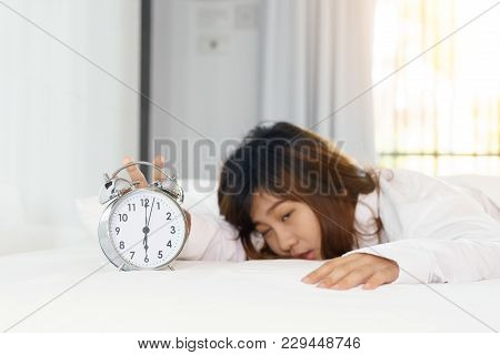 Sleepy Woman Trying Turn Off Alarm Clock In The Morning.