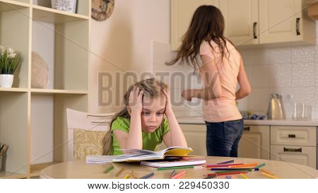 Woman Is Engaged In Domestic Duties While Her Daughter Doing Boring Homework, Stock Footage