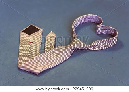 Pink Tie Is Tied In The Shape Of A Heart On A Gray Background.