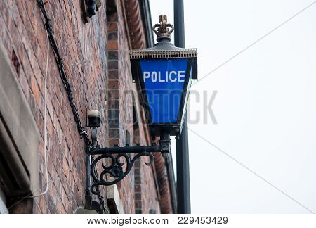 A Blue Police Light On The Wall Outside A Police Station