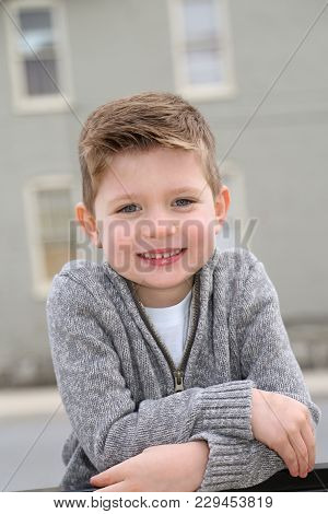 Happy Young Kid With A Big Smile In A Grey Sweater With Neutral Building In The Background
