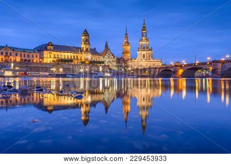 Dresden, Germany classical cathedrals and spires on The Elbe River at night.
