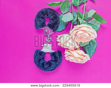 Fur Handcuffs (a Sex Toy For Adults) And A Bouquet Of Three Light Roses Are On A Purple Background.