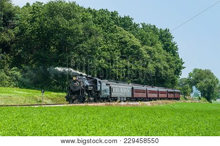 Steam Train Engine With Passenger Cars Letting Passengers Off On A Warm Summer Day